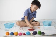 Boy play dough. A boy plaing colorful dough on white background Stock Photo