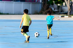 Boy play football on the blue concrete floor. Stock Image