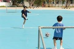Boy play football on the blue floor Stock Photography