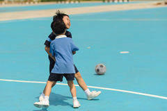 Boy play football on the blue floor Stock Images