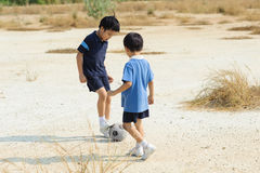 Boy play football on the dry soil ground Royalty Free Stock Images