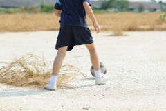 Boy play football on the dry soil ground Royalty Free Stock Photography