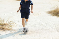 Boy play football on the dry soil ground Stock Images
