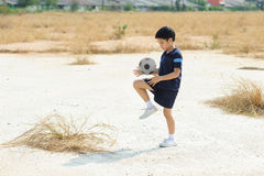 Boy play football on the dry soil ground Stock Photography