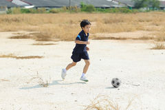 Boy play football on the dry soil ground Stock Photo