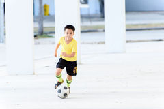 Boy play football under the empty building Stock Images