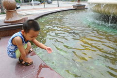 The boy play with fountain water Royalty Free Stock Images