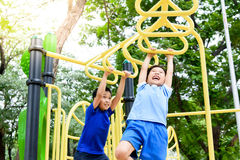Boy play with hang yellow bar. Young asian boy hang the yellow bar by his hand to exercise at out door playground under the big tree Stock Images