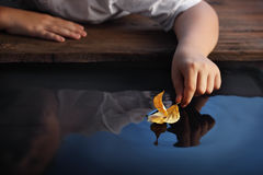 Boy play in leaf ship Royalty Free Stock Images