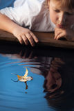 Boy play with leaf ship in water royalty free stock photos