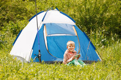 Boy play with mobile phone in summer park, hi sits near the tent Royalty Free Stock Images