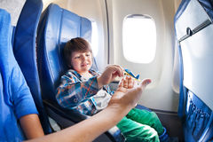 Boy play with mother in jet plane seat Royalty Free Stock Images