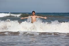 Boy play with ocean waves Stock Photography