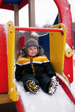 Boy play on the playground. In the winter Royalty Free Stock Photo