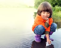 Boy play in puddle. Summer day stock images