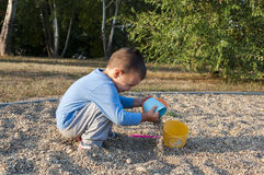 Boy play in the sand. With his toys Royalty Free Stock Image