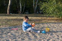 Boy play in the sand. Boy sitting in the sand and playing with his toys Royalty Free Stock Photos