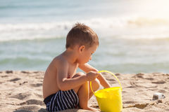 Boy play with sand on summer beach Stock Photo