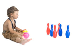 Boy play skittles on white Royalty Free Stock Photo