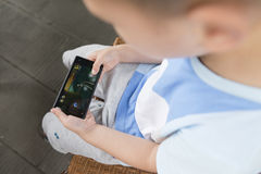 Boy indulging in smartphone Stock Image