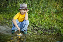 Boy play with toy ship in water, chidlren park play with boat in Stock Image