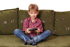 Boy play video game. Boy sitting on bed and play video game Stock Photos