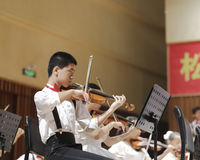 A boy play the violin carefully. Songbai elementary school students of amoy city performances report orchestral music. the picture shows a boy playing the violin Stock Images