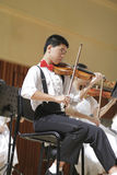 Boy play the violin carefully. Songbai elementary school students of amoy city performances report orchestral music. the picture shows a boy playing the violin Royalty Free Stock Images