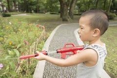 Boy play water gun Stock Photos