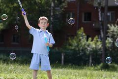 Boy is played with soap bubbles in the street Stock Images