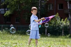 Boy is played with soap bubbles in the street Royalty Free Stock Images
