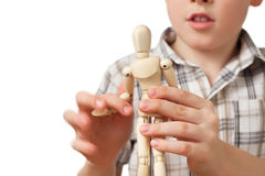Boy is played by wooden little manikin Royalty Free Stock Photo