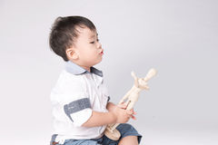 Boy is played by wooden little manikin Royalty Free Stock Image