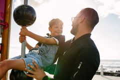 Father and son enjoying vacation. Boy in a playful mood sitting on a play equipment near seafront. Man with his son on a vacation enjoying near the sea Stock Photography