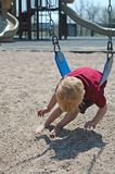 Boy in playground. Small boy playing on a swing in playground Stock Photography