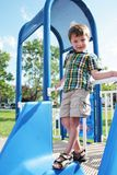 Boy on playground. Smiling boy in summer attire, standing at the top of a playground sliding board Stock Photo