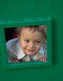 Boy at playground. Happy childhood. Little boy at playground looking through little window Stock Photography