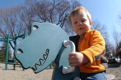 BOY ON PLAYGROUND. A two year-old boy rides a dinosaur piece of playground equipment Royalty Free Stock Photo