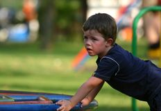 Boy at playground. Young boy at playground on roundabout royalty free stock photo