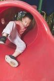 Boy sliding on playground Stock Image