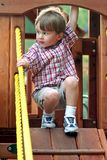 Boy on Playground Equipment. A boy is playing on playground equipment Stock Photo