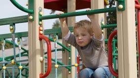 Boy on playground equipment. stock video