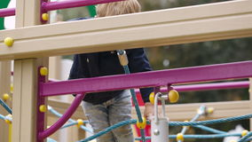 Boy on playground equipment. Stock Photos