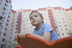Boy In Playground With Residential Buildings In Background Royalty Free Stock Images