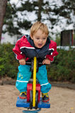 Boy on playground ride stock image