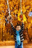 Boy on playground rings. Nice black boy 8 years old hanging on the rings on playground in the autumn park Royalty Free Stock Image