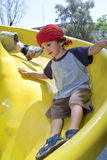 Boy on a playground slide. Boy on a yellow playground slide Royalty Free Stock Image