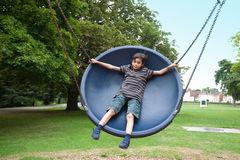 boy in playground swing stock image
