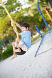 Boy on a playground swing. Young boy on a playground swing Royalty Free Stock Photography