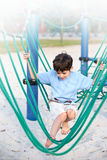 Boy on a playground swing Stock Images